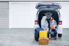Parents with their children ready for vacation. Young parents with their children ready for vacation while sitting together in the car trunk Royalty Free Stock Photo