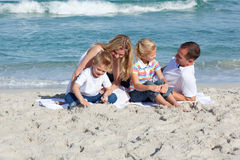 Parents with their children sitting on the sand Stock Photography
