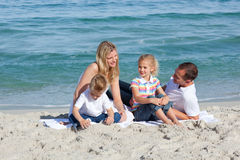 Parents with their children sitting on the sand Stock Images