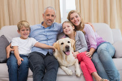 Parents and their children on sofa with labrador Royalty Free Stock Photo