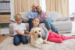 Parents and their children on sofa with labrador Stock Images