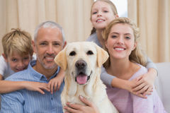 Parents and their children on sofa with labrador Royalty Free Stock Photos