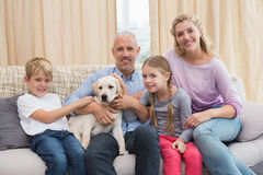 Parents with their children on sofa playing with puppy Royalty Free Stock Photos