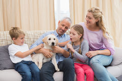 Parents with their children on sofa playing with puppy Stock Image