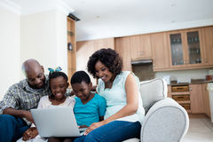 Parents and their children using laptop in living room. At home Stock Photos