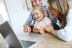 Parents with their daughter laughing in front of laptop Stock Images