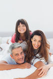 Parents with their daughter lying on bed Stock Image
