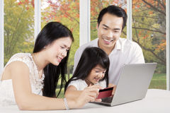 Parents and their daughter paying online Stock Image