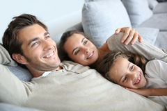 Parents and their daughter relaxing on sofa Royalty Free Stock Photo