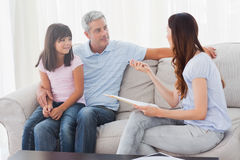 Parents with their daughter sitting on sofa Royalty Free Stock Photo