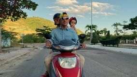 Parents with their little kid riding motorcycle on sunny city street stock video footage