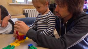 Parents and their little son playing with colorful construction set together. Construction or railroad travel concepts stock video footage