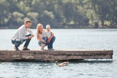 Parents with their little son on a walk near the lake. People and nature royalty free stock photos