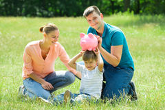 Parents With Their Son Holding Piggy Bank stock images