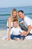 Parents with their son sitting on the sand. Portrait of cheerful parents with their son sitting on the sand at the beach Stock Photography