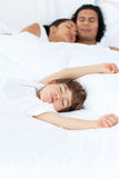 Parents and their son sleeping on the bed. In parent's bedroom stock images