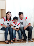 Parents and their son watching a football