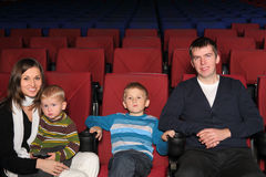 Parents with their two sons in cinema. Happy parents with their two sons in the cinema Stock Photography