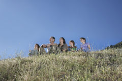 Parents With Three Kids On Hill Against Blue Sky Stock Photography