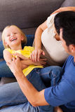 Parents tickling daughter. Parents tickling little daughter on sofa Stock Photos