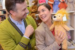 Parents-to-be shopping choosing plush for their kid. Leisure Royalty Free Stock Photos