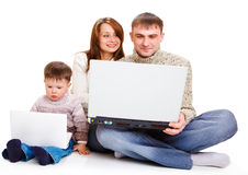 Parents and toddler with laptops. Parents with large laptop and toddler boy with a small one Royalty Free Stock Image
