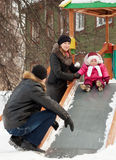 Parents with  toddler playing on slide. Happy parents with  toddler playing on slide in winter Stock Photography