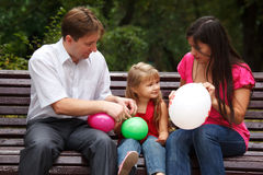 Parents together with daughter on bench in park Stock Images