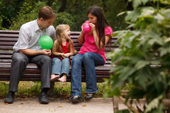 Parents together with daughter on bench in park Royalty Free Stock Photography