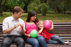 Parents together with daughter on bench in park Royalty Free Stock Photo