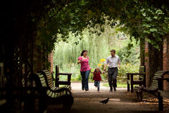 Parents together with daughter run on tunnel. From ivy in summer garden Stock Photography