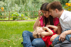 Parents together with girl have rest in garden Stock Photos