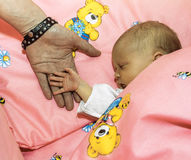 Parents touch her newborn child at the  crib. Parents touch her newborn child at the pink crib Stock Photography