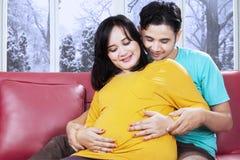 Parents touchant leur bébé dans le ventre Photographie stock libre de droits