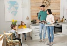 Parents traitant des enfants avec le four cuit au four photo stock