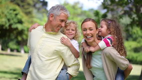 Parents turning with their children on their back Royalty Free Stock Photo