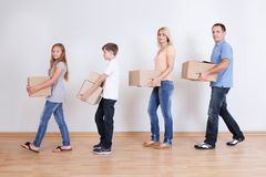 Parents And Two Children With Cardboard Boxes Stock Photography