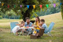 Parents of two children listening to their son talking during family picnic. Dedicated young parents of two children listening to their funny son talking while royalty free stock photography