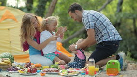 Parents with two children on a picnic in the woods. Daughters playing patty-cake stock video