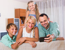 Parents with two children posing in home interior Stock Photos