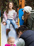 Parents with two daughters playing at children's slide Royalty Free Stock Photos