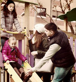 Parents with two daughters playing at children's slide Royalty Free Stock Photography