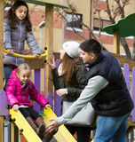 Parents with two daughters playing at children`s slide Royalty Free Stock Photo