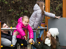 Parents with two daughters playing at children`s slide Royalty Free Stock Image