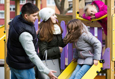 Parents with two daughters playing at children's slide Royalty Free Stock Image