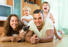 Parents and two daughters with Siamese. Family portrait of parents and two daughters lying on the floor at home with Siamese. Focus on man Stock Photography