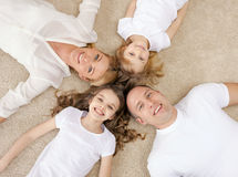 Parents and two girls lying on floor at home Royalty Free Stock Photography