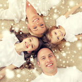 Parents and two girls lying on floor at home Stock Image