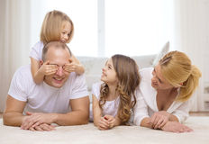 Parents and two girls lying on floor at home Stock Photo