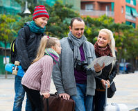 Parents with two kids and baggage with map Stock Photos